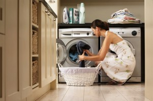 Woman loading washing machine in kitchen